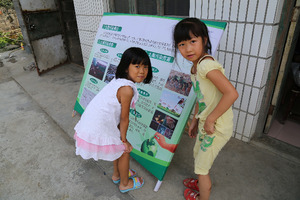 Local children looking at an educational poster about pollution